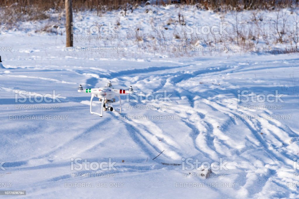 drone Phantom with a video camera flies in the woods in winter. Quadcopter with camera stock photo