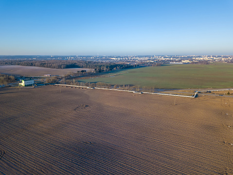 Drone photo of agricultural fields, heating networks, gas station on the outskirts of the city on a Sunny snowless winter day, the city is visible in the distance