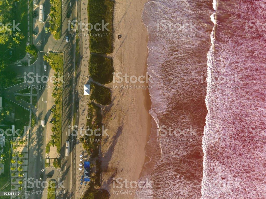 Drone photo of beach in Barra da Tijuca, Rio de Janeiro, Brazil. Waves crashing with whitewash, the golden sand and the boardwalk beaches can be seen. Colored Light leak filter applied - Zbiór zdjęć royalty-free (Architektura)