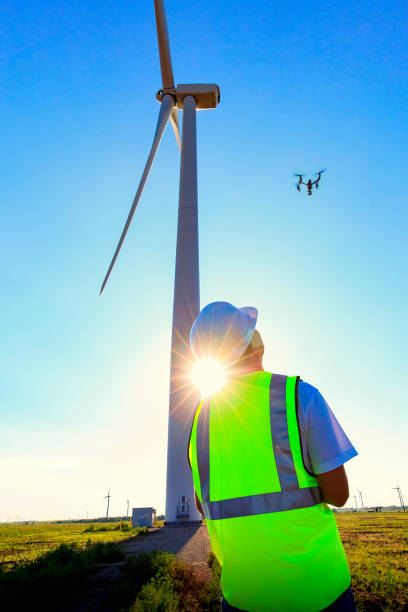 Drone Pilot Operating UAV During Wind Turbine Inspection Drone pilot wearing his safety vest operating a UAV on Kansas wind farm. drone point of view stock pictures, royalty-free photos & images