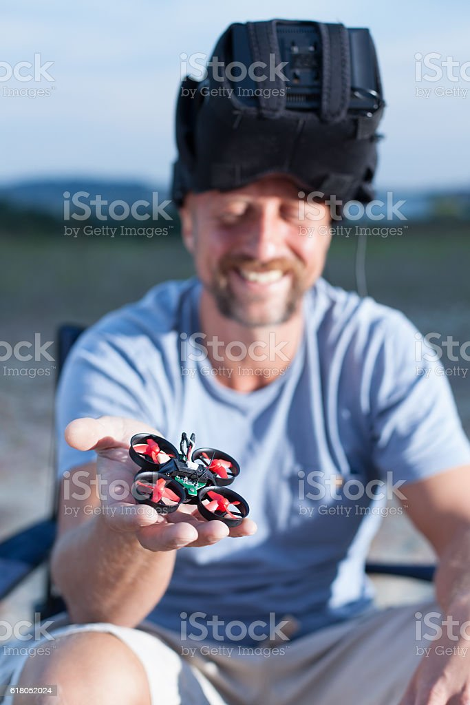 drone pilot with goggles holding a micro drone stock photo