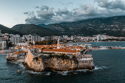 Drone point of view at the old town Budva surrounded by a big ancient wall and the city of Budva with its new buildings and marina in the background seen during the twilight.