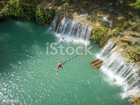 Aerial view of man jumping right into waterfalls, Philippines Greens and turquoise colors, people nature travel destinations concept