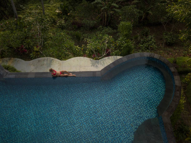 drone point of view of young woman by the edge of an infinity pool, ubud, bali enjoying tropical climate vacations in asia - mulher natureza flores e piscina imagens e fotografias de stock