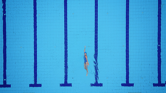 istock Drone point of view on swimming pool and female backstroke swimmer 697521154