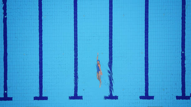 drone point of view on swimming pool and female backstroke swimmer - swimming stock pictures, royalty-free photos & images