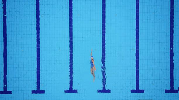 Drone punto de vista sobre la piscina y nadador de espalda femenino - foto de stock