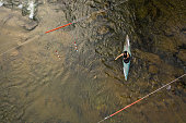Drone point view of  kayaking white water rapids, young female athlete rowing in kayak