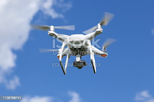 Hochheim, Germany - April 28, 2016: A quadrocopter Phantom 4 of Chinese technology company DJ Innovations (DJI). DJI was founded in 2006, it produces unmanned, remote controlled aerial vehicles for many fields of application, e.g. aerial photography and videography. Mounted camera and gimbal on the bottom of the device.