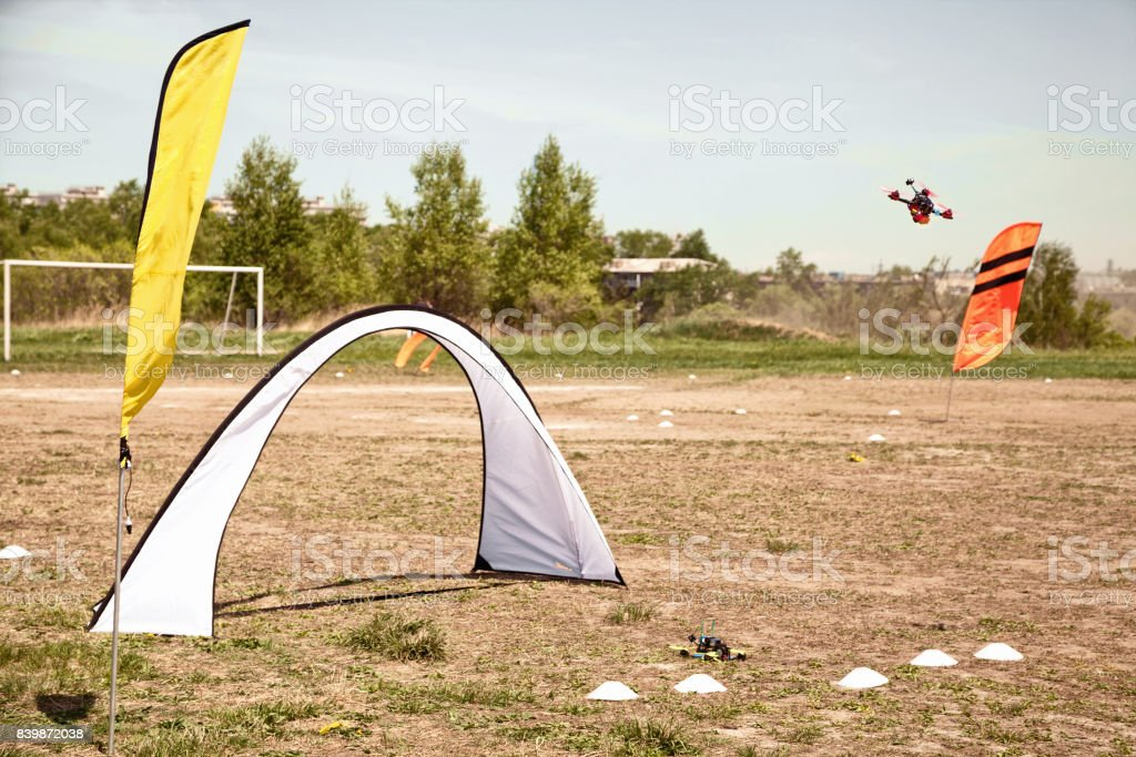 Drone racing in a field with gates and flags. stock photo
