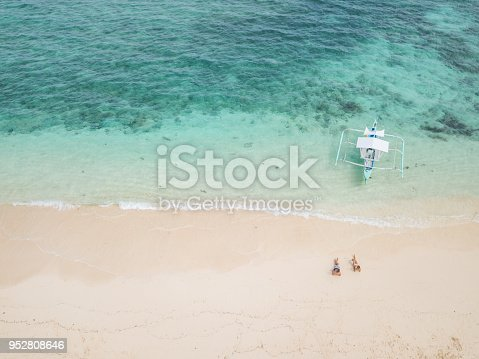 Drone shot aerial view of young couple lying down on idyllic tropical beach , shot in the Philippines. Drone concept high angle view.  People travel vacations dreamlike places concept.