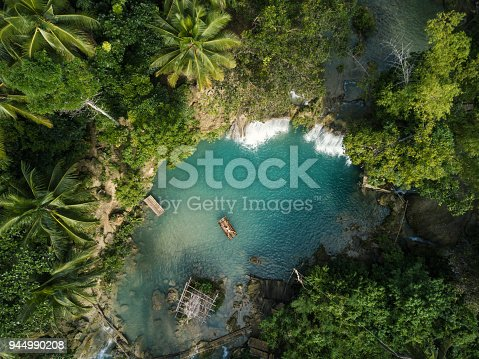 istock Drone shot aerial view of young woman bamboo rafting at tropical waterfall 944990208