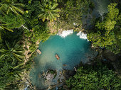 High angle view from drone shot aerial view of young woman bamboo rafting on a beautiful waterfall on Siquijor Island in the Philippines. People travel nature outdoor activities concept. One person only enjoying outdoors and tranquillity in a peaceful environment, solo traveler concept