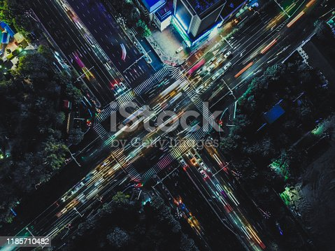 istock Drone Shot of City Street Crossing at Night 1185710482
