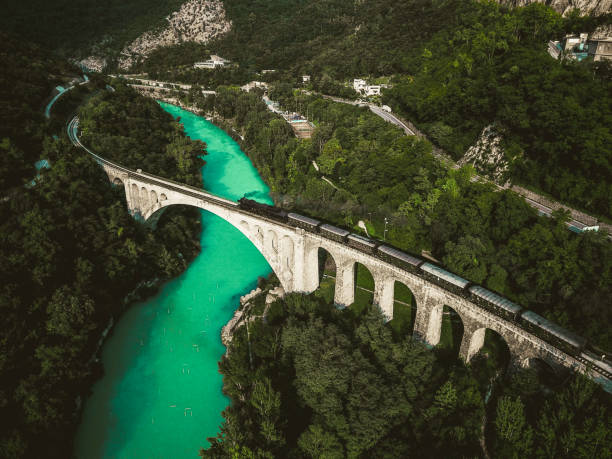 tir de drone historique vieux train passant solkan pierre pont sur la rivière soča - slovénie photos et images de collection