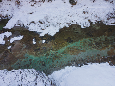 Aerial drone shot of snowy and icy winter landscape in the oetschergraeben