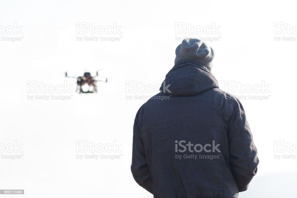 drone user piloting his drone outdoors isolated on white