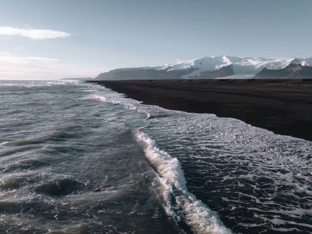 Drone view at Iceland black beach with mountains at background stock photo