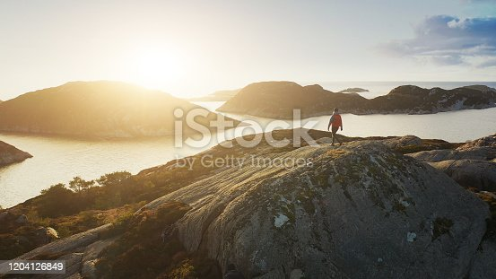 Drone view of a woman outdoor adventures: hiking in Norway, on the mountain by a fjord