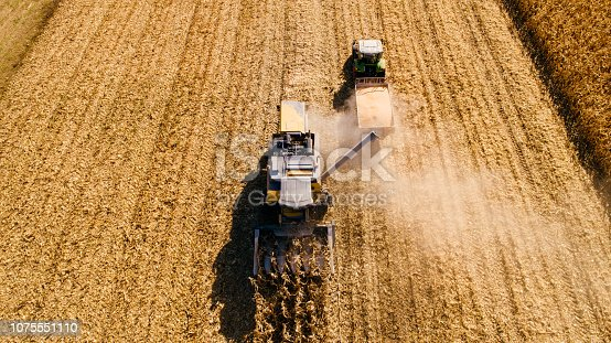 1072634078 istock photo Drone view of agriculture machinery working the fields 1075551110