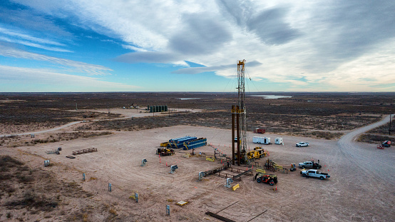Drone View Of An Oil Or Gas Drill Fracking Rig Pad with Beautiful Cloud Filled Sky