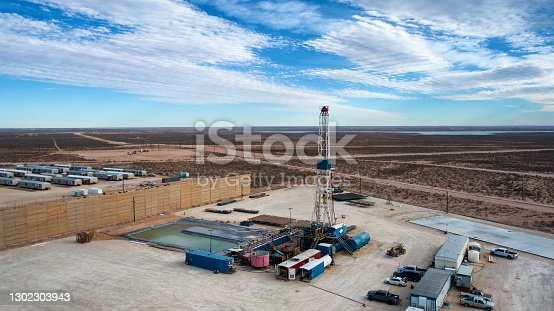 istock Drone View Of An Oil Or Gas Drill Fracking Rig Pad with Beautiful Cloud Filled Sky 1302303943
