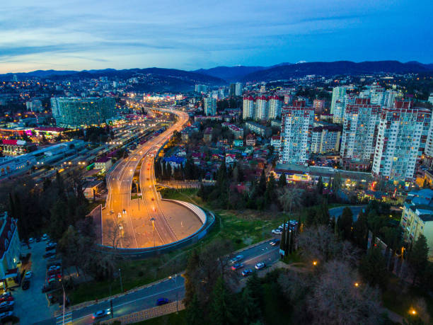 Drone view of Doubler of Kurortnyy Prospekt highway, Sochi, Russia Beautiful drone view of city, mountains and Doubler of Kurortnyy Prospekt highway at twilight, Sochi, Russia sochi stock pictures, royalty-free photos & images