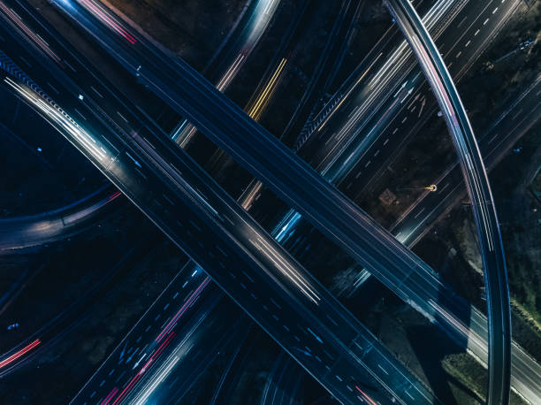 Drone View of Road Intersection at Rush Hour Drone Point View of City Street Crossing at Rush Hour long exposure stock pictures, royalty-free photos & images