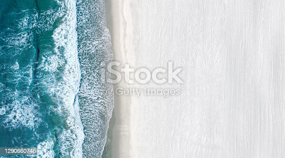 istock Drone view of sea waves rolling on an empty white beach 1290660746