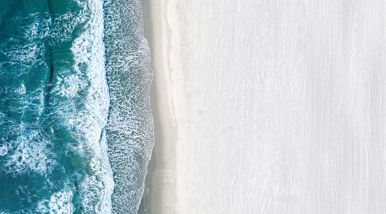 Drone view of ocean blue water with sea waves rolling on an a large and empty white beach. Copy space on the right side.