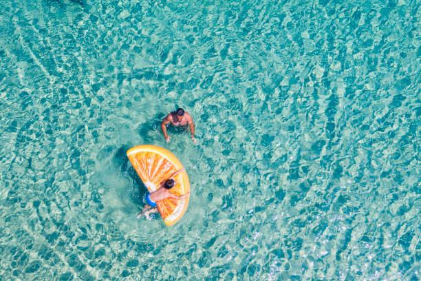 vista drone das pessoas nadando - laguna - fotografias e filmes do acervo