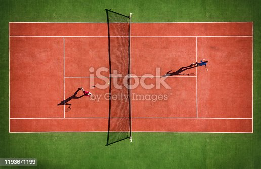 Drone view of tennis match from above with player's shadow