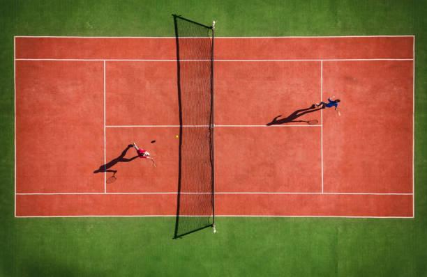 Drohnenansicht des Tennisspiels von oben mit Spielerschatten – Foto
