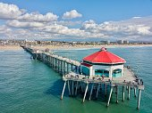 Aerial drone view of the Huntington Beach Pier against blue sky with clouds