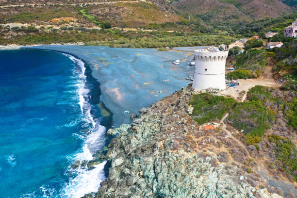 Drone view of the panoramic seascape of black pebble beach of Nonza, Cap Corse France Drone aerial view of Plage de Nonza with the Genoese tower, the long black beach at the foot of the cliffs on which the small town of Nonza stands, the famous village on the coast of Cap Corse. Tourism and vacations concept. rocky coastline stock pictures, royalty-free photos & images