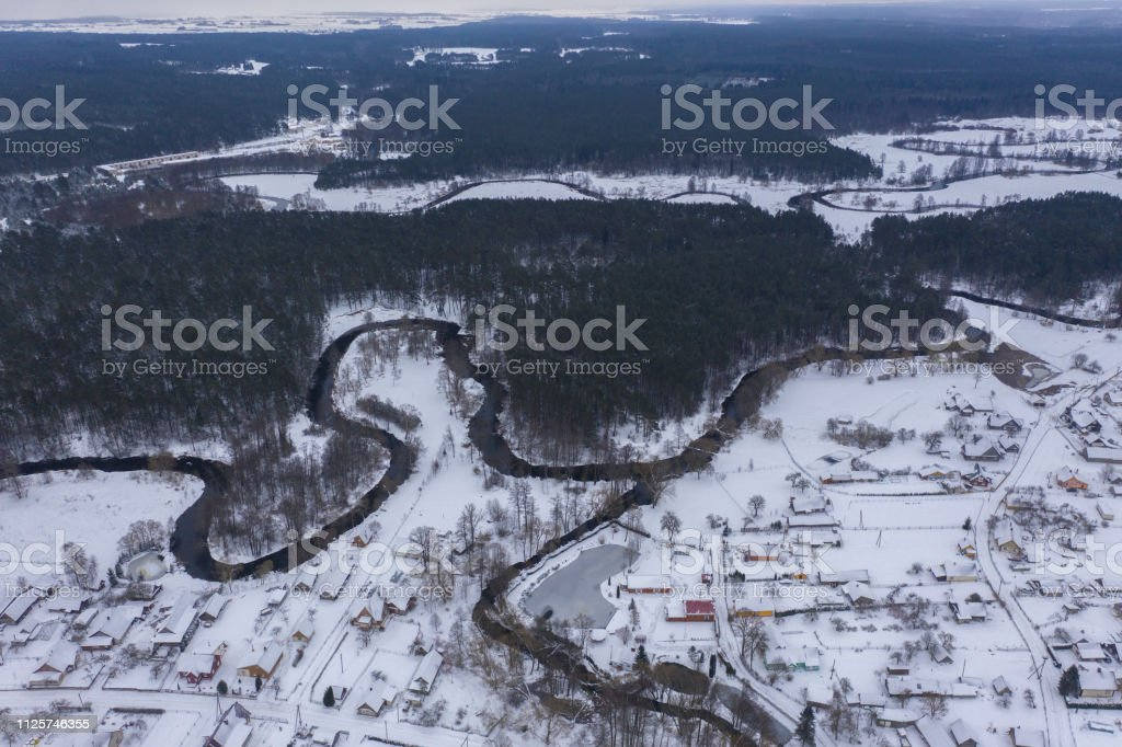Drone view of winter forest and curving river during cloudy day