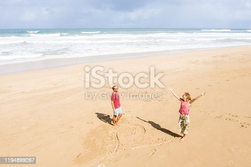 Drone view of young couple standing on drawn heart on beach in Hawaii, USA Love romance sharing concept