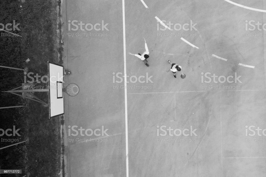 Drone view on two friends playing basketball stock photo