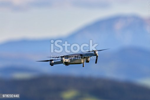 Drone with camera flying over mountain fields. Aerial photography and videography. Drone quad copter with high resolution digital camera in the air