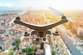 Drone with digital camera flying over a city at sunset: 3d illustration