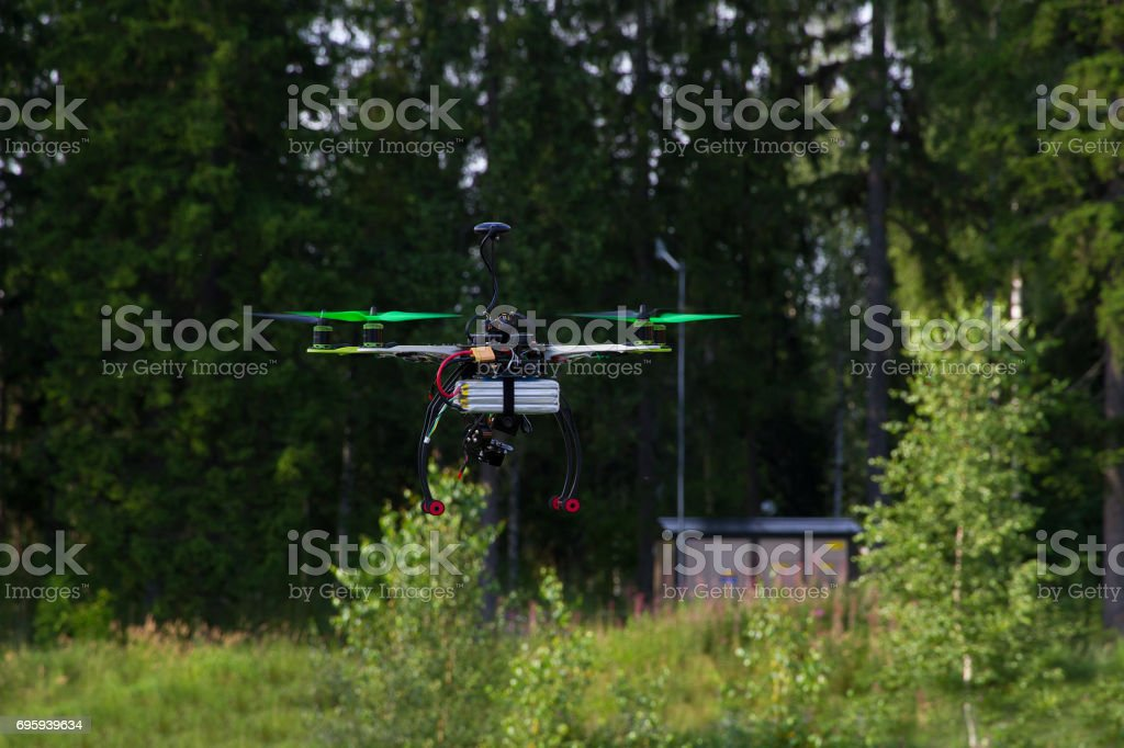 Drone with green props is flying in a bright summer day. Forest as a background. стоковое фото