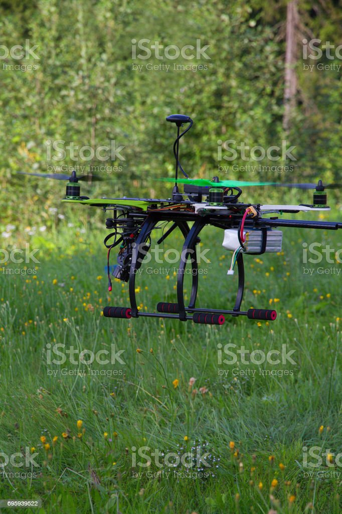 Drone with green props is flying. Summer day. Green forest and green field with small flowers as a background. стоковое фото