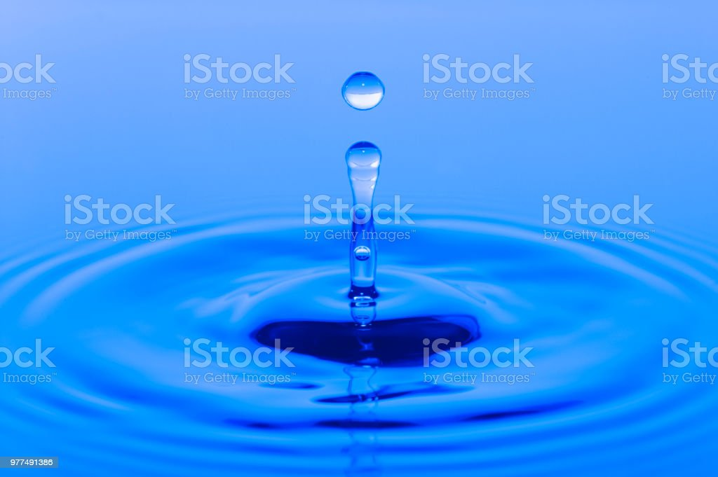 drop is falling and splashing on blue surface of water stock photo