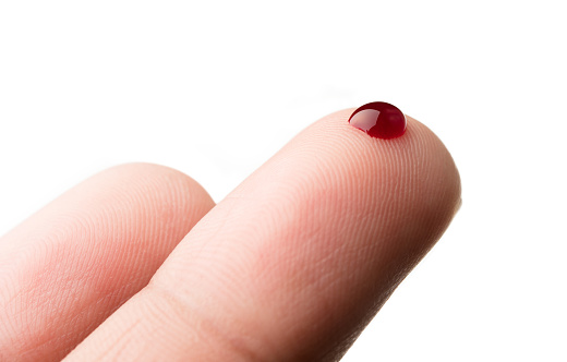 istock Drop of blood on finger on white background 877270936