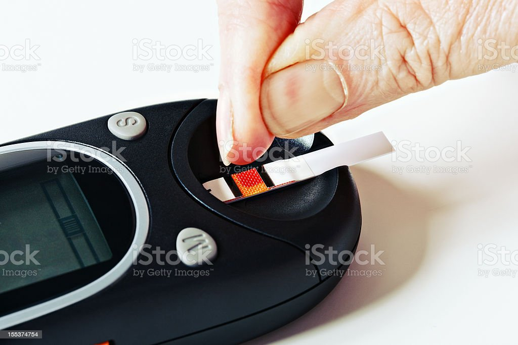 Drop of blood on test strip in glucometer royalty-free stock photo