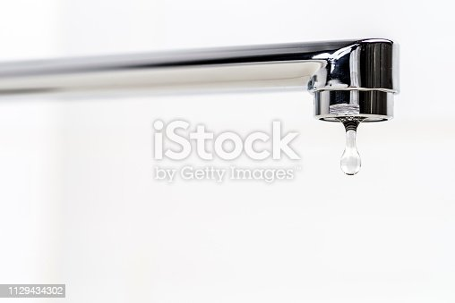 A drop of clear water is dripping from the tap.