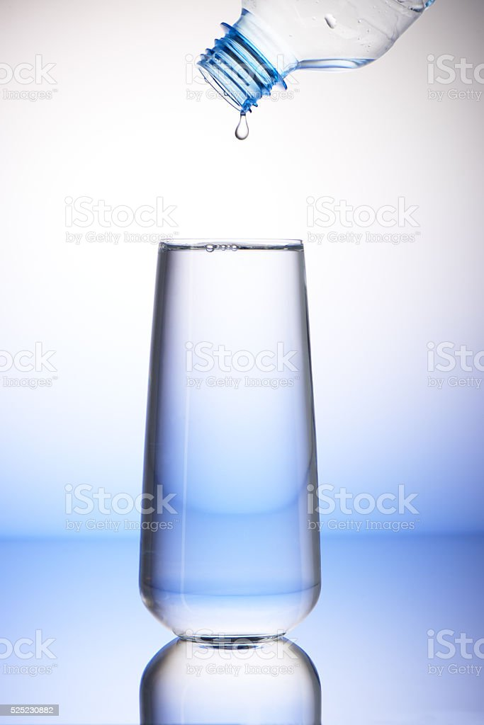 Drop of water falling from plastic bottle into full drinking glass...