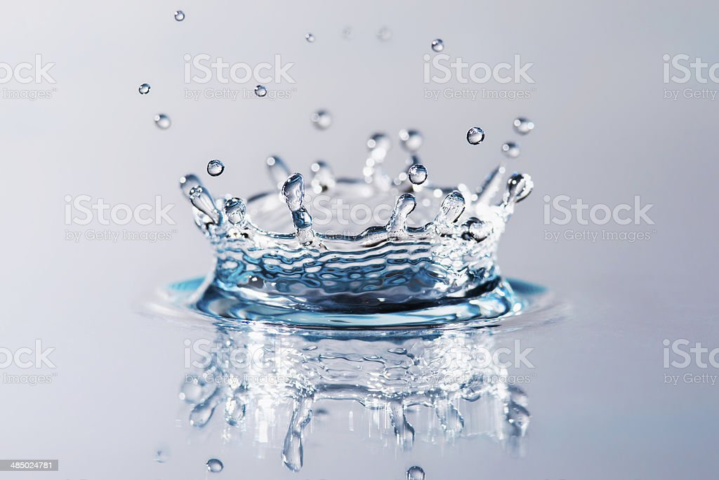 Drop of water falling with splashes stock photo