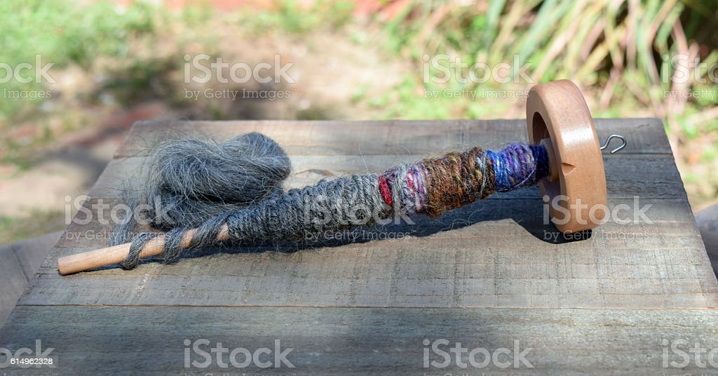 Drop spindle for spinning sheep wool into yarn stock photo