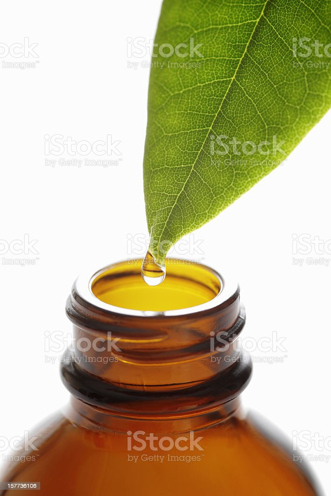 Droplet falling from green leaf into brown bottle royalty-free stock photo
